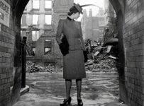 Lee Miler, Model wearing Digby Morton suit, shot through arch revealing bomb damage. © Lee Miller Archives